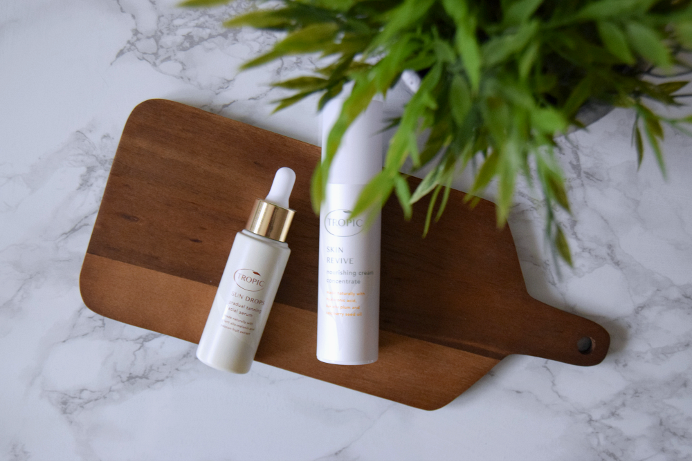 flat lay of Tropic Skin Care products on a wooden slate atop a marble table with a plant nearby